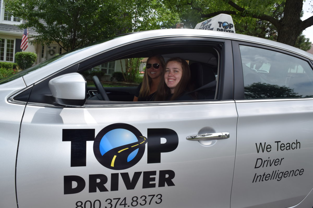 Fun with drivers ed. Teen in car with driving instructor.