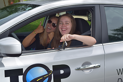 Top Driver student and teacher in car. Teacher is giving a thumbs up.
